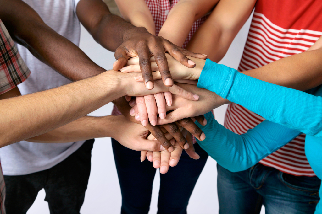 Team of friends showing unity with their hands together - CASA of